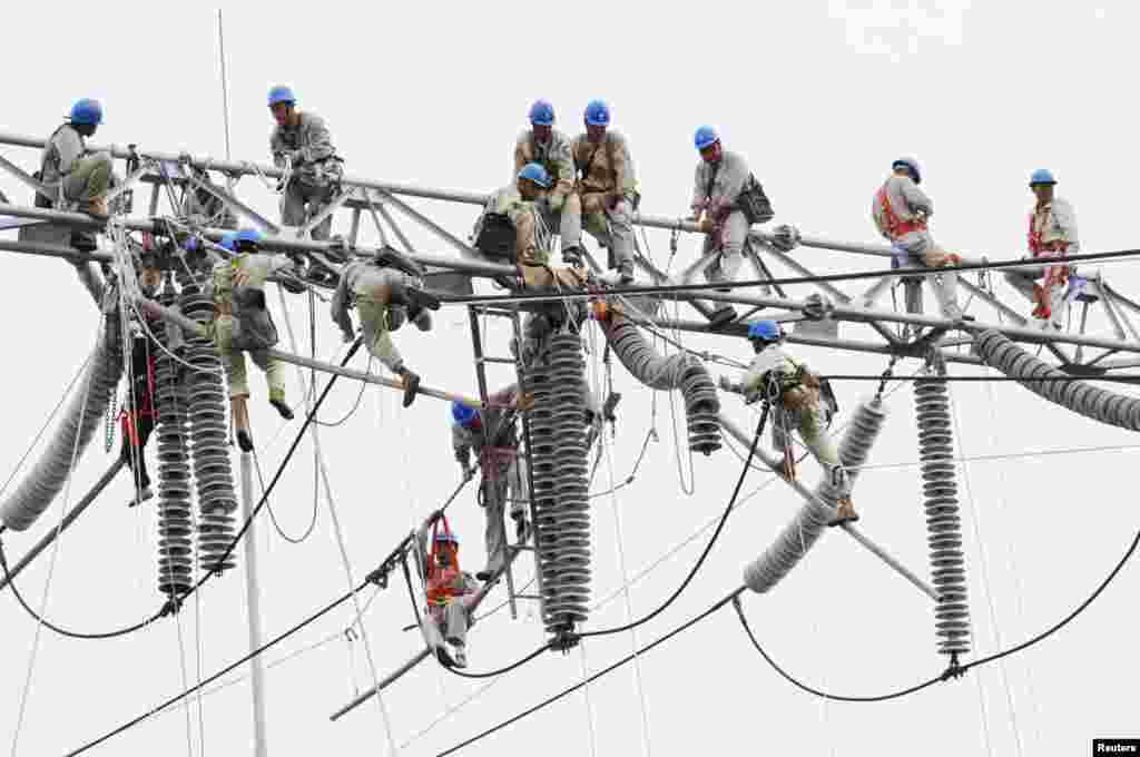 Chinese workers climb equipment to perform maintenance work at an electric-power-transformation substation in Xuzhou, in Jiangsu Province. (Reuters/China Daily)