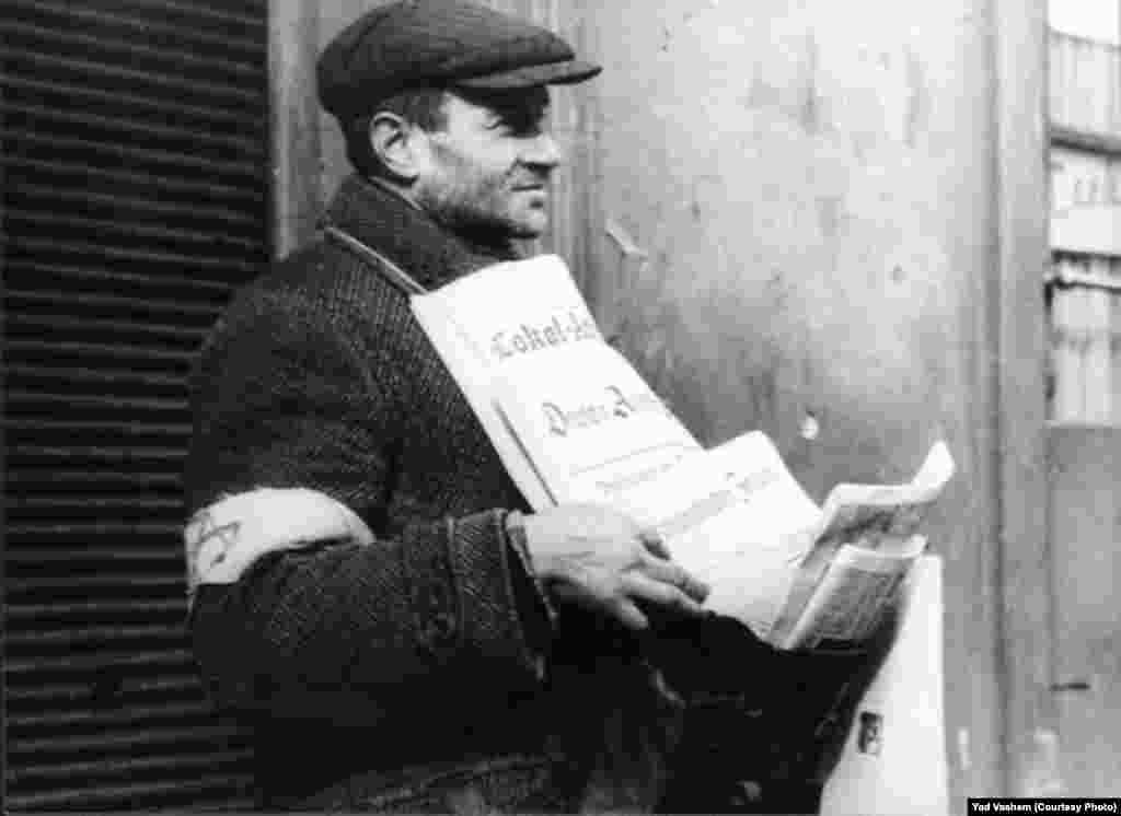 A Jew in the ghetto displays newspapers for sale.