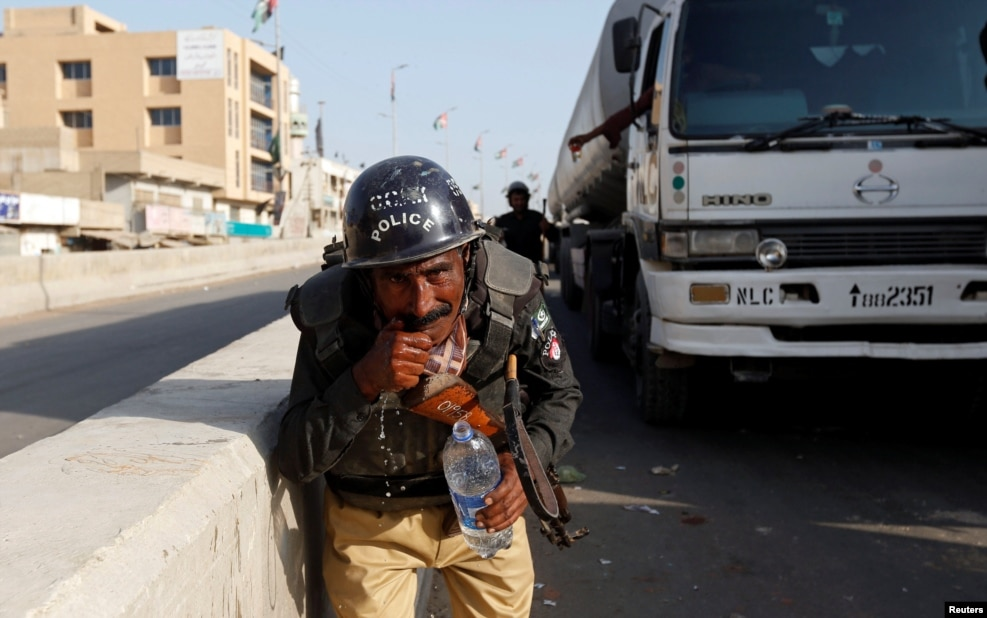 A policeman washes away the effects of tear gas fired by police after Shi'ite Muslim men blocked the main national highway and railway tracks to protest raids of both Sunni and Shi'ite religious seminaries and the detention of an unspecified number of people, in Karachi, Pakistan. (Reuters/Akhtar Soomro)