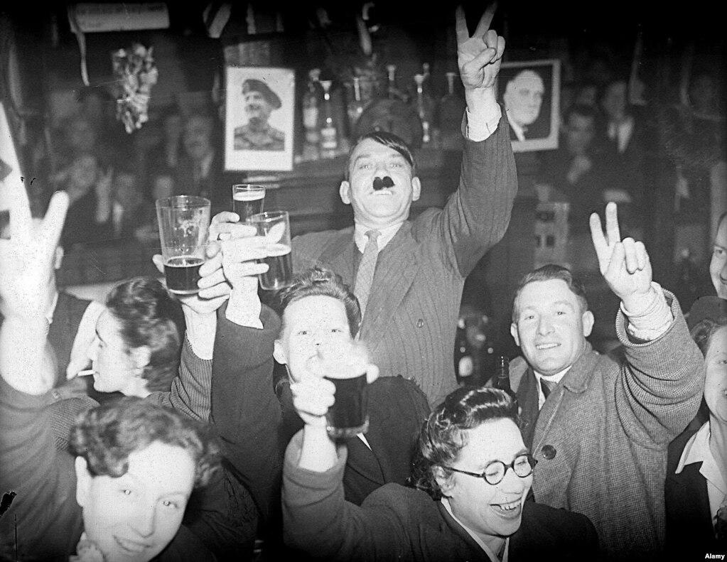 Молодь Лондона, включно з молодим хлопцем, який пародіює Гітлера, розпивають пиво в пабі лондонського району Ламбет