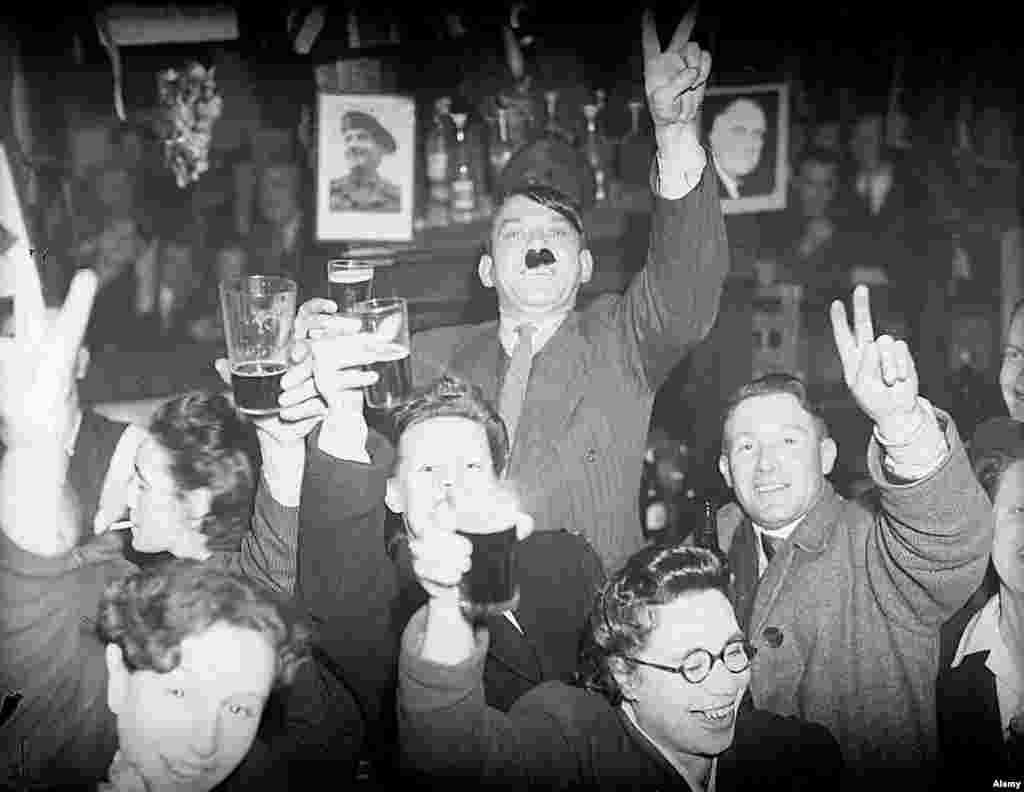 Londoners, including a man with his nostrils stuffed with Hitler-like bristles, gleefully sink beers in a pub in the Lambeth part of London.