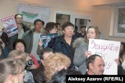 Защитники урочища Кокжайляу держат в руках плакаты. Алматы, 19 января 2015 года.