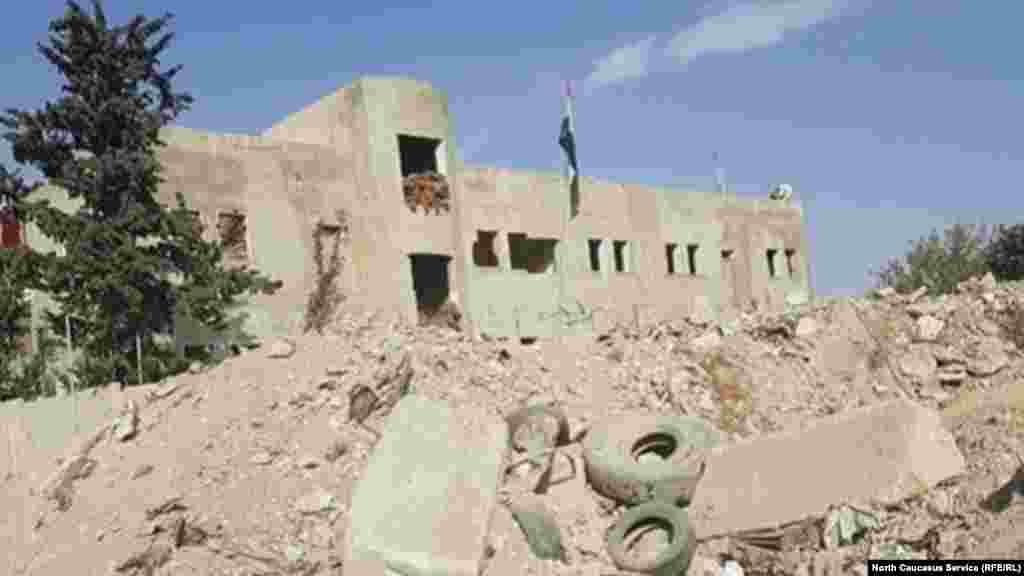 Флаг Сирийской арабской республики на руинах разрушенного здания