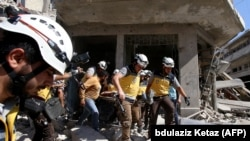 Members of the Syrian Civil Defense body known as the White Helmets pull bodies and wounded people out from under rubble following an air strike on Maaret al-Numan in the Syria's northwestern Idlib Province on July 22.
