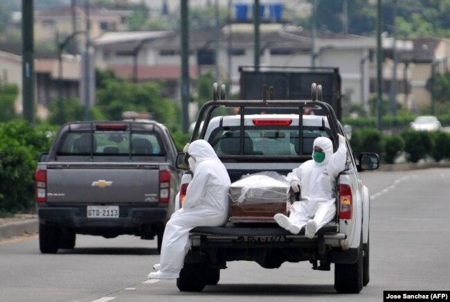 Эквадор, Гуякиль, 8 апреля 2020 года. Два человека в защитных костюмах перевозят в кузове пикапа тело умершего от COVID-19