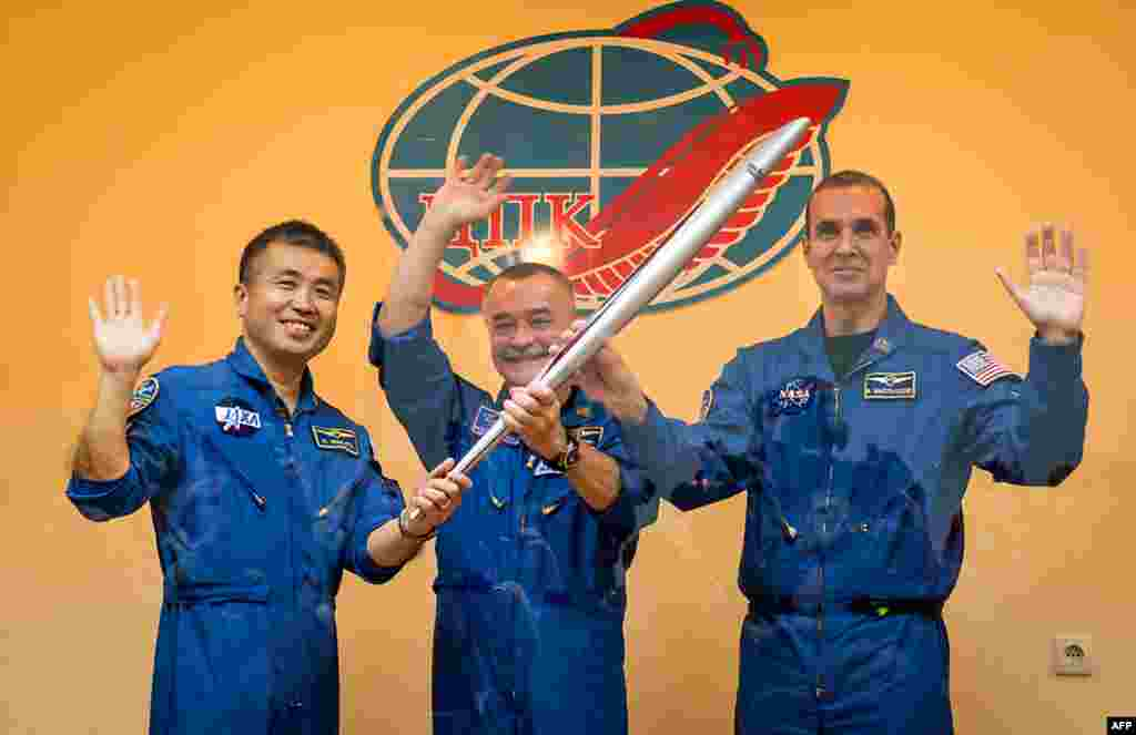 This photo from Kazakhstan shows (left to right) Soyuz Flight Engineer Koichi Wakata from Japan, Commander Mikhail Tyurin from Russia, and Flight Engineer Rick Mastracchio (from the U.S.) holding the Olympic torch prior to boarding the Soyuz TMA-11M rocket on November 7, 2013.