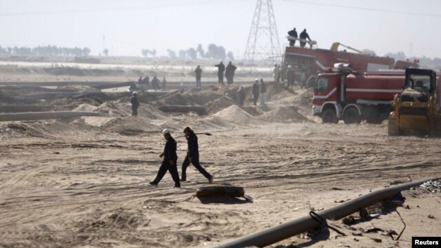Employees of the Iraqi state-run South Oil Company (SOC) walk near a damaged pipeline in Al-Basrah province in December.