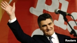 Croatian center-left opposition leader Zoran Milanovic celebrates after exit polls showed his coalition had won a majority in parliamentary elections.