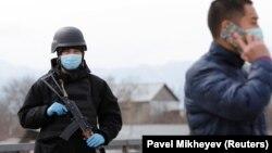 Представитель правоохранительных органов в защитной маске на блокпосту возле Алматы. 24 марта 2020 года.