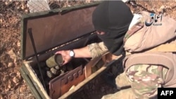 A video grab purportedly shows an IS militant displaying the contents of a crate of grenades reportedly intended for Kurdish militias but which fell into the hands of Islamic State militants near the town of Kobani.