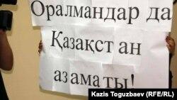 """Плакат с обращением к Тимуру Кулибаеву на казахском языке """"Оралманы - тоже граждане Казахстана!"""". Алматы, 4 октября 2011 года."""