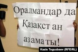 Оралмандар проблемасына арналған жиынға қатысушы ұстап тұрған жазу. Алматы, 4 қазан 2011 жыл. (Көрнекі сурет)