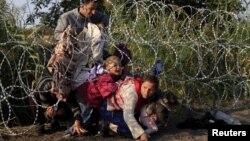 Сирійські мігранти прориваються крізь колючий дріт на кордоні з Сербії до Угорщини, архівне фото