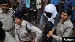 Пострадавшая швейцарская туристка направляется на медицинское обследование в сопровождении полиции. Штат Мадхья-Прадеш, 16 марта 2013 года.