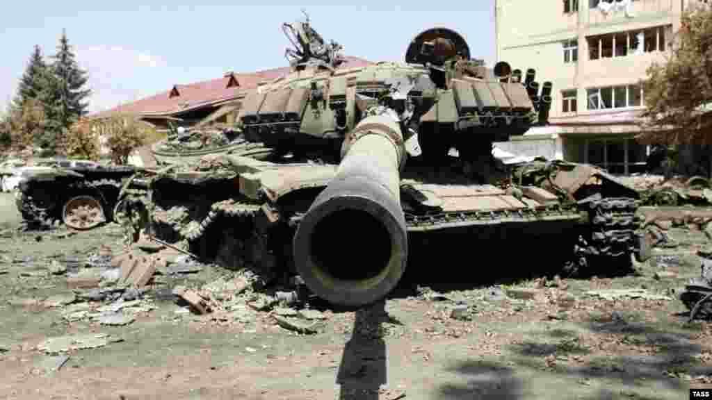 14 августа: уничтоженный грузинский танк среди руин Цхинвали. Российские и грузинские официальные лица договорились о плане прекращения огня 12 августа, который через два дня подписали руководители Южной Осетии и Абхазии