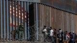 Migranți din țări din America Centrală se uită prin gardul de la frontiera cu Mexic, lângă punctul de trecere El Chaparral, Baja, California