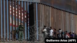 Мигранты из Латинской Америки у заграждения на границе США.