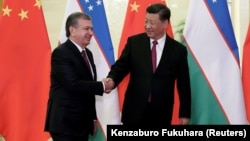 Uzbek President Shavkat Mirziyoev (left) meets Chinese President Xi Jinping in Beijing on April 25.