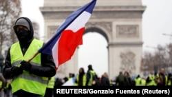 Наразылық акциясына қатысушы Франция туын ұстап тұр. Париж, 15 желтоқсан 2018 жыл.