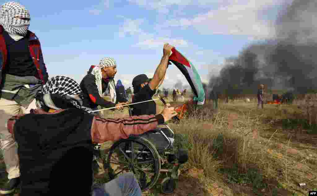 A picture taken on December 15 shows wheelchair-bound Palestinian demonstrator Ibrahim Abu Thurayeh waving a Palestinian flag amid smoke from flaming tires during a protest along the Gaza-Israel border against the U.S. recognition of Jerusalem as Israel's capital. (AFP)