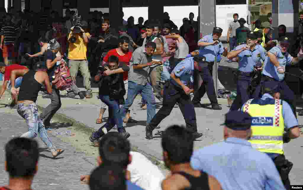 Croatian policemen run as Syrian and Afghan migrants clash at the train station in Beli Manastir on September 18.