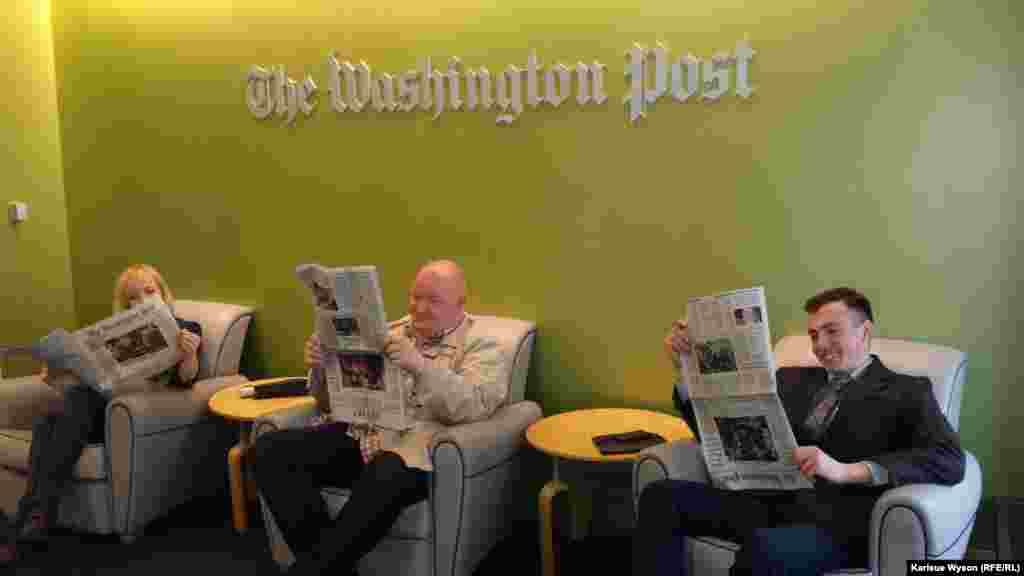 "Sedletska (l), Beliaev and Gabidulin during their visit to ""The Washington Post,"" reading the latest edition from top to bottom..."