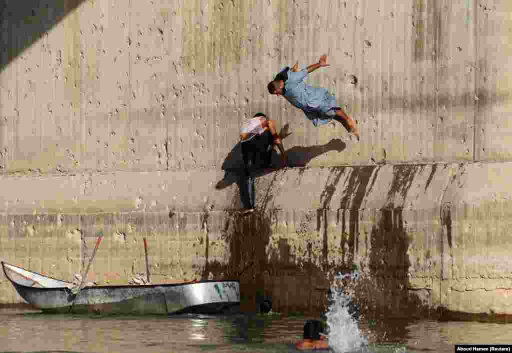 A man jumps in the Euphrates River during hot weather in Raqqa, Syria. (Reuters/Aboud Hamam)