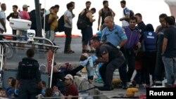 Адзін зь мігрантаў перадае дзіця ў рукі афіцэра грэцкай берагавой аховы пасьля выратавальнай апэрацыі, у порце на грэцкім востраве Кос, 17 жніўня 2015 году