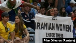 "Darya Safai holds a banner reading ""Let Iranian women enter their stadiums"" at the Iranian men's volleyball match against Egypt on August 13."