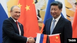 Chinese President Xi Jinping attends a signing ceremony with Russian President Vladimir Putin (left) at the Great Hall of the People in Beijing in September 2015.