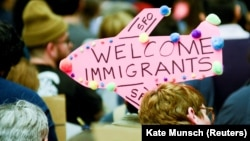 Demonstrators hold welcome signs for immigrants at San Francisco's international airport on January 28 as anger mounted over President Donald Trump's executive order.