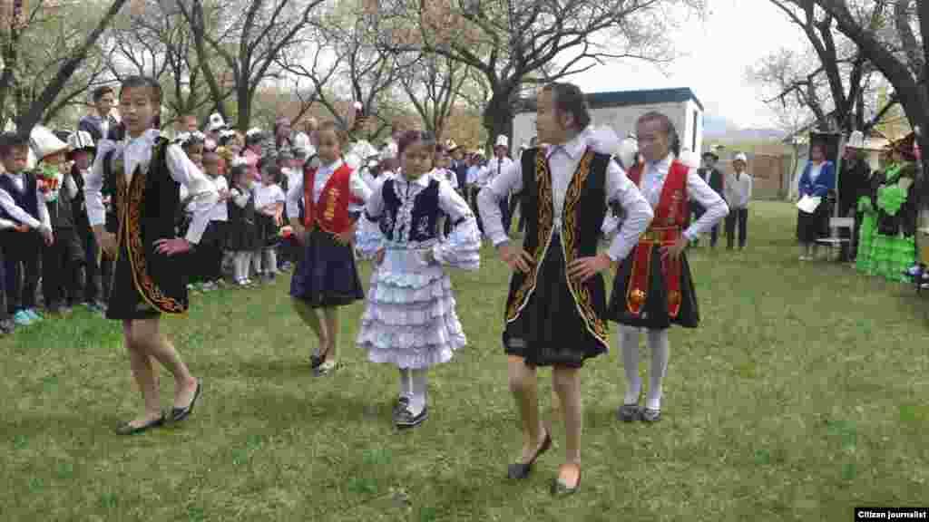 Кыргыз кыздар тажикстандык конокторго бий тартуулап жатат.