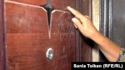 Баксулу Отарбаева показывает дверь, которую выбивала полиция. Кульсары, 14 сентября 2012 года.