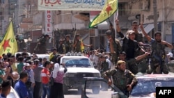 Тел-Абьяд шаарын алууга катышкан күрт күчтөрүнүн Сириянын түндүк-чыгышындагы Камишли шаарчасындагы парады. 24-июнь, 2015-жыл.