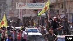 Таль Абияд қаласының бір бөлігін содырлардан босатқан сириялық күрдтер қала көшелерімен шерулетіп өтіп барады. Сирия, 26 маусым 2015 жыл.