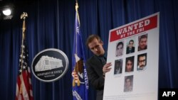 WASHINGTON, DC - MARCH 24: A Department of Justice employee put up a poster of the seven indicted hackers prior to a news conference for announcing a law enforcement action March 2