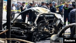 The wreckage of a car is seen at the site of bombing near a government office in Baghdad's Karkh district on May 30.
