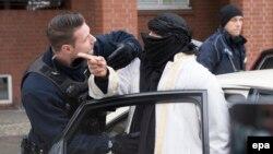 Германский полицейский разговаривает с мужчиной на улице Берлина