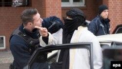 Германский полицейский разговаривает с мужчиной на улице Берлина.