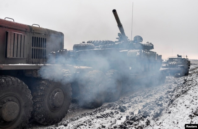 A Ukrainian military truck tows a tank damaged during fighting with pro-Russian separatist forces outside Debaltseve on February 10.