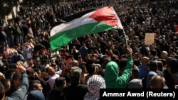 Worshippers wave a Palestinian flag after Friday prayers on the compound known to Muslims as Noble Sanctuary and to Jews as Temple Mount in Jerusalem's Old City, December 8, 2017