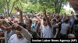 Iran -- A group of protesters chant slogans at the old grand bazaar in Tehran, Iran, Monday, June 25, 2018.