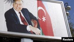 Azerbaijan -- A woman walks past a board displaying late President Haydar Aliyev in Baku, 13Oct2010