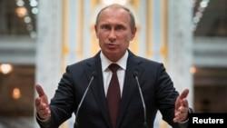 Russian President Vladimir Putin gestures as he speaks to the media after talks with Ukrainian President in Minsk on August 27.