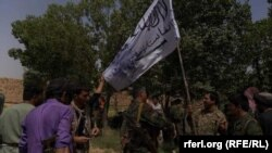 The Afghan forces hold a Taliban flag after overrunning an insurgent hideout in Marjah on July 22.