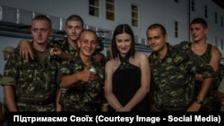 Anastasia Prykhodko poses with Ukrainian soldiers on the front line.