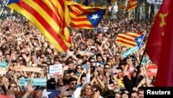 Люди стежать за голосуванням на великому екрані біля парламенту Каталонії в Барселоні, Іспанія, 27 жовтня 2017 року