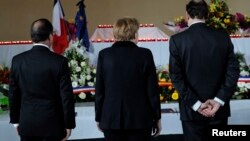 French President Francois Hollande (left), German Chancellor Angela Merkel (center), and Spain's Prime Minister Mariano Rajoy pay their respects on March 25 at a makeshift morgue prepared for the 150 victims who died in the crash.