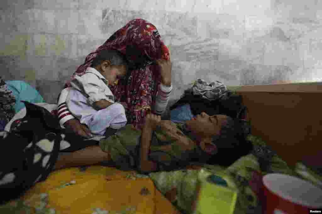 A woman displaced from a drought-stricken area of Pakistan sits with her children, who are suffering stomach infection, at the Civil Hospital in Mithi, in Sindh Province. (Reuters/Akhtar Soomro)