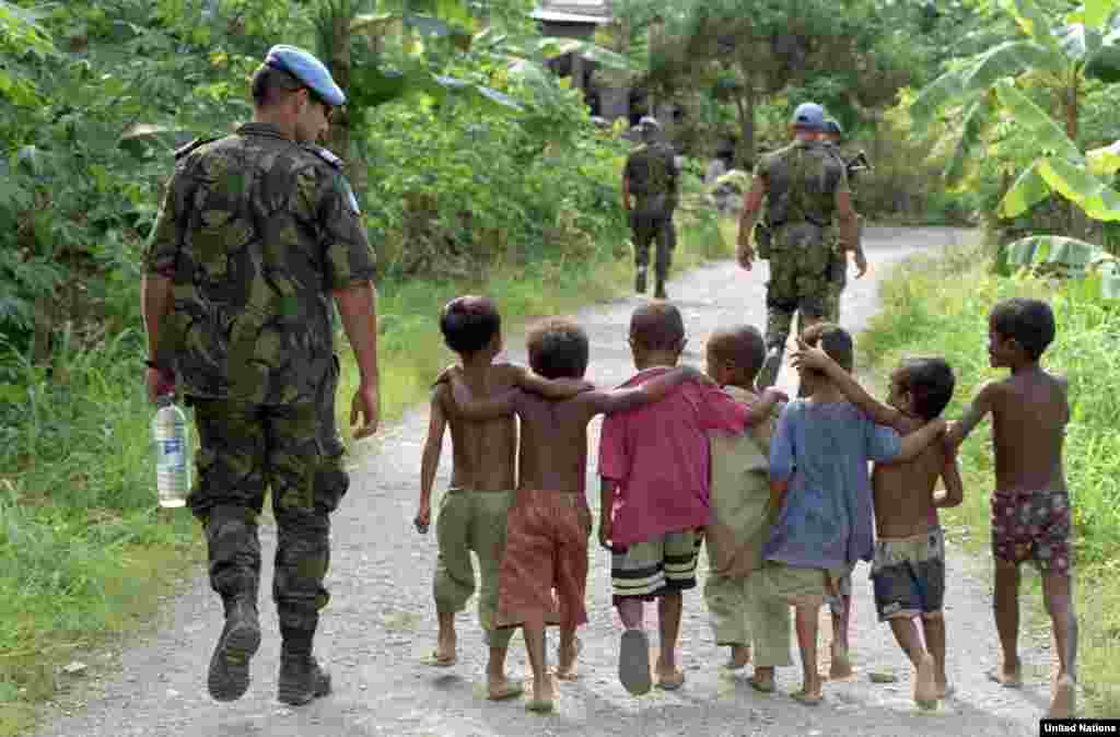 Portuguese members of the United Nations Transitional Administration in East Timor (UNTAET) are accompanied by a group of local children as they conduct a security patrol in the Becora district of Dili in March 2000.